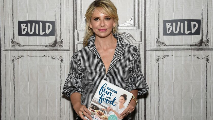 "Actress Sarah Michelle Gellar with her cookbook, ""Stirring Up Fun With Food."""