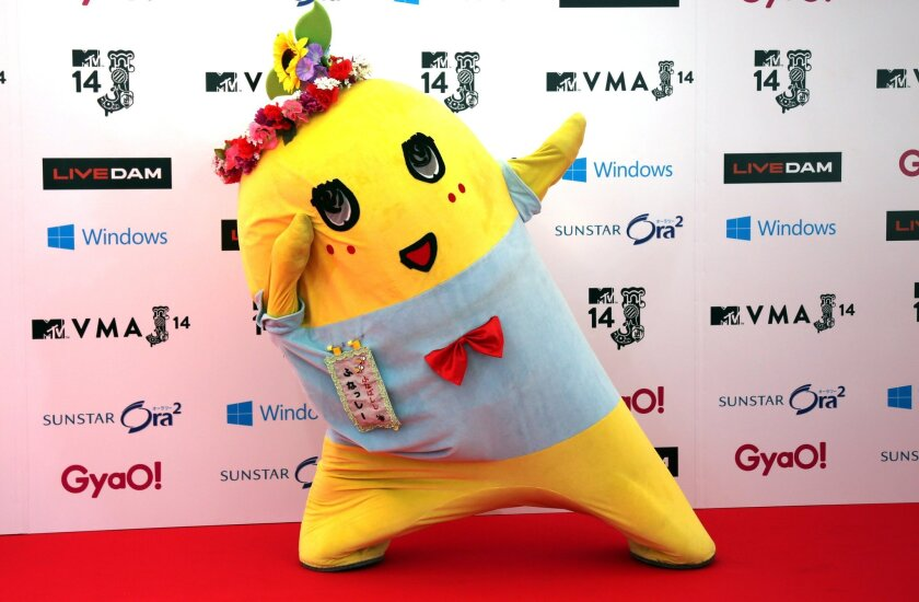 "FILE - In this June 14, 2014 file photo, Japanese mascot character ""Funassyi"" poses for photographers on the red carpet at MTV Video Music Awards Japan ceremony at Makuhari Amphitheater in Chiba near Tokyo. In a bright yellow, stretchy bodysuit, the pear-fairy jumps up and down frantically and talks in a rapid-fire, high-pitched voice, shouting ""nashi!"" (pear) at the end of each sentence. Funassyi appears regularly on TV and is releasing a CD from Universal Music Japan. The character reportedly earned 200 million yen ($2 million) last year. (AP Photo/Eugene Hoshiko, File)"