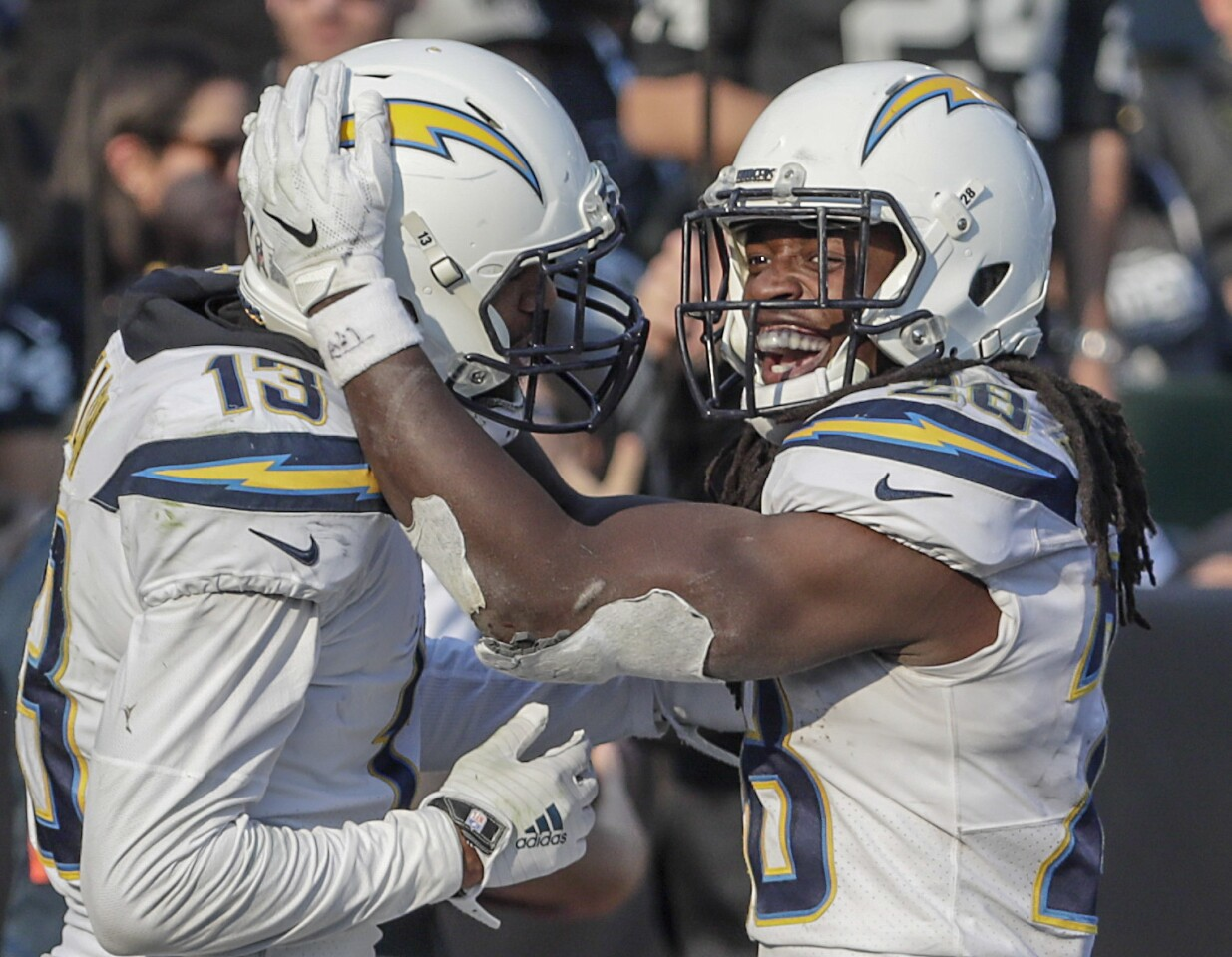 Chargers running back Melvin Gordon III celebrates with teammate Keenan Allen after scoring a touchdown early in the third quarter at Oakland-Alameda County Coliseum on Sunday.