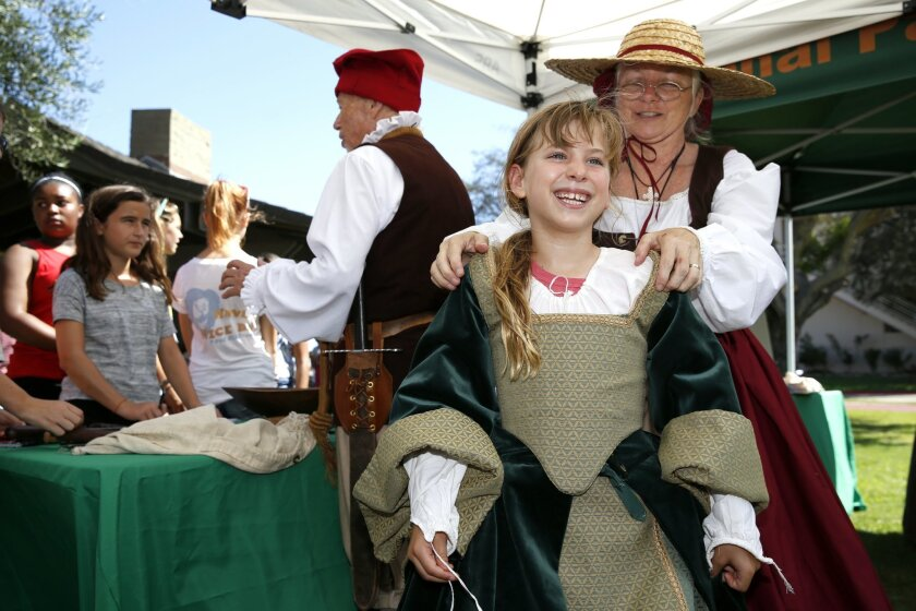 NL_CabrilloFest_347569   September 21, 2015.  San Diego, CA. Photo by Nancee E. Lewis..Living history volunteers Louise Lucas (right) helps Sofia Warner, 8, into a period costume that women wore during the 1600's  during Fleet Week Cabrillo Festival which took place at Ballast Point.  Lucas is a vo