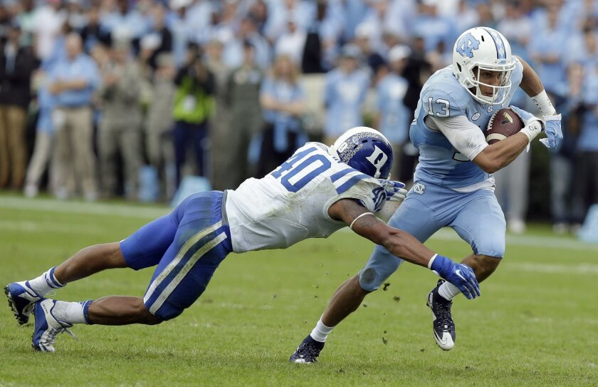 North Carolina's Mack Hollins (13) runs the ball as Duke's Dwayne Norman (40) reaches for the tackle during the first half of an NCAA college football game in Chapel Hill, N.C., Saturday, Nov. 7, 2015. (AP Photo/Gerry Broome)