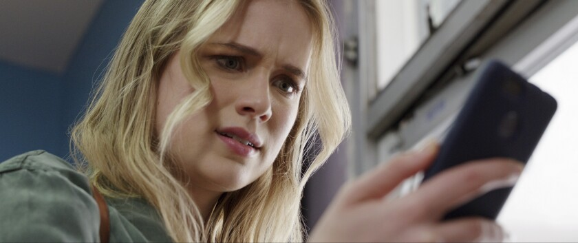 "Elizabeth Lail checks her phone in the movie ""Countdown."""
