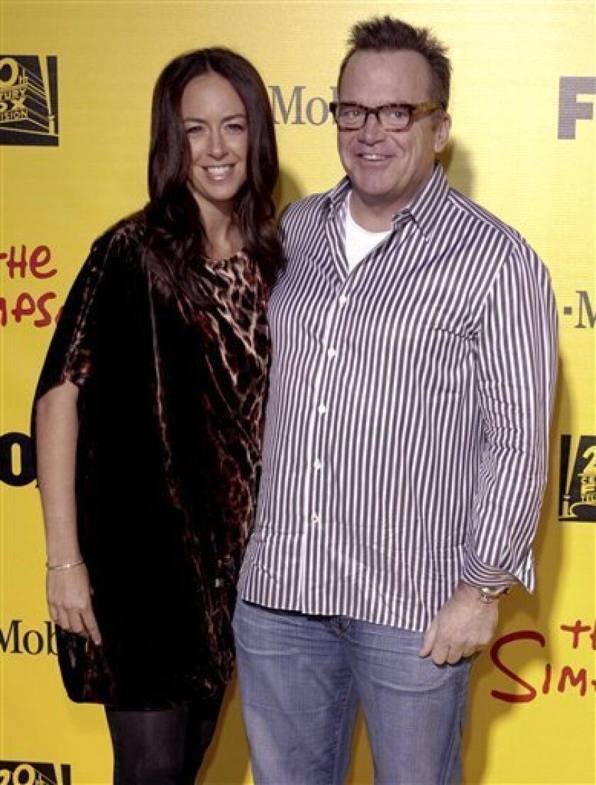 FILE - In this Oct. 18, 2009 file photo, actor Tom Arnold, right, and Ashley Groussman arrive at The Simpsons Treehouse of Horror XX & 20th Anniversary Party in the Barker Hangar in Santa Monica, Calif. (AP Photo/Alaric Lambert, file)
