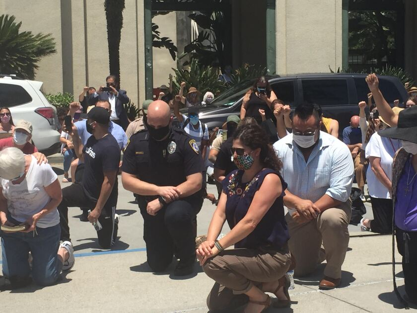 Escondido Police Chief Ed Varso is seen kneeling at City Hall on Wednesday during a demonstration.