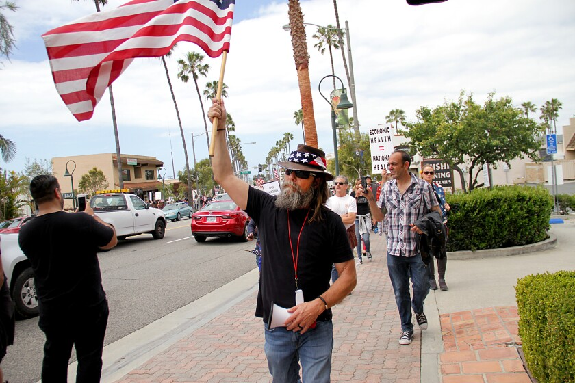 In protest of the state's stay-at-home order, Alan Hostetter leads a march through Downtown San Clemente on April 21, 2020.