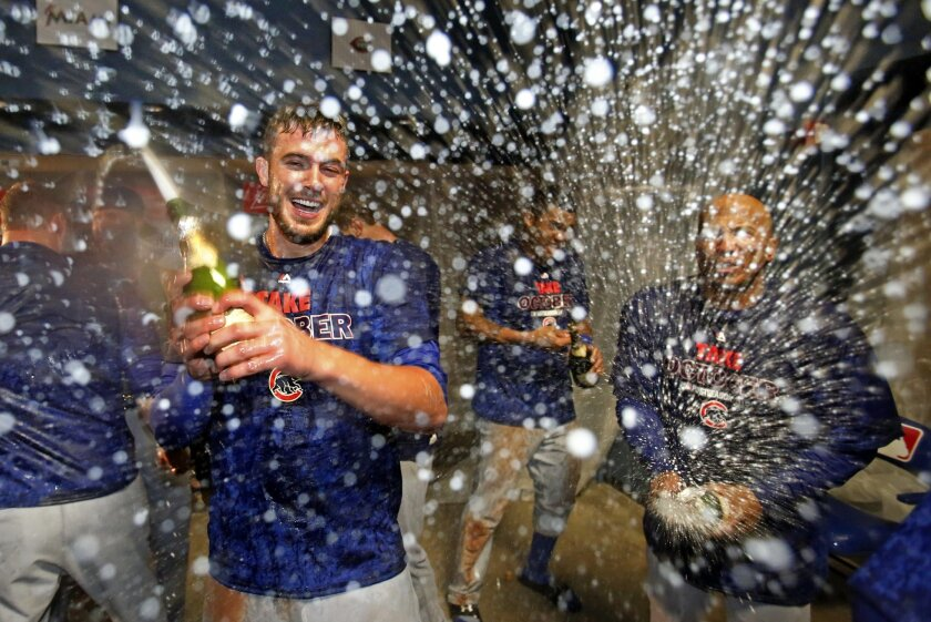 Chicago Cubs' Kris Bryant, left, celebrates with teammates in their locker room after a 4-0 win over the Pittsburgh Pirates in the National League wild card baseball game Wednesday, Oct. 7, 2015, in Pittsburgh. The Cubs advance to face the St. Louis Cardinals in the National League Division Series. (AP Photo/Gene J. Puskar)