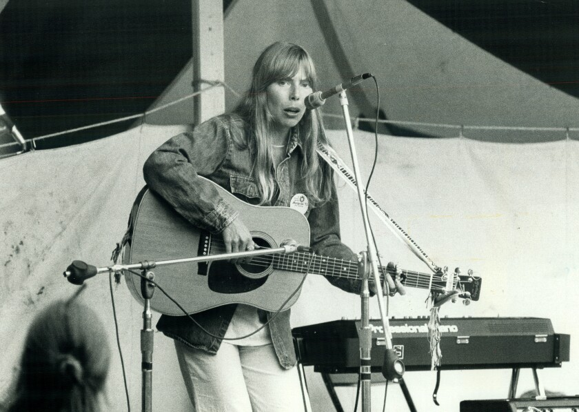 A young Joni Mitchell plays guitar and sings into a microphone