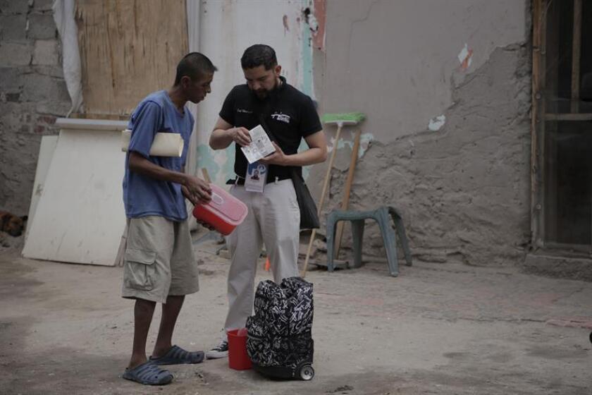 Adán (i) conversa con un promotor de salud el 9 de agosto de 2018, en Ciudad Juárez (México). Tristeza y cuerpos marcados, jeringas y dosis. EFE