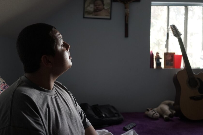 """In this March 10, 2016, photo, student Cuauhtemoc Lara sings from his bedroom in East Los Angeles. Cuauhtemoc discovered singing Mexican ballads known as corridos as an escape from the gangs and violence in his neighborhood. He is now enrolled in a singing class at Stevenson Middle School, which for years had no arts classes for most students. The Los Angeles Unified School District is trying to enlist Hollywood executives and music studios to """"adopt"""" LA Unified schools and provide them with equipment, mentorships and training. (AP Photo/Christine Armario)"""