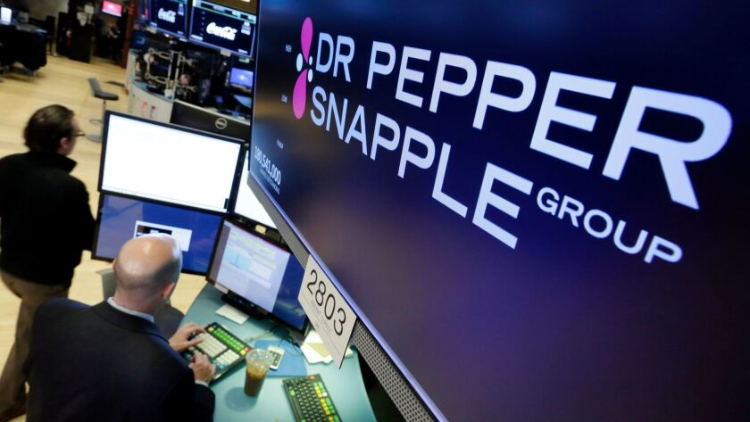 Dr Pepper Snapple Group soared 22.4% to $117.07 after it agreed to be acquired by Keurig for $16.6 billion, including debt. Above, on the floor of the New York Stock Exchange,