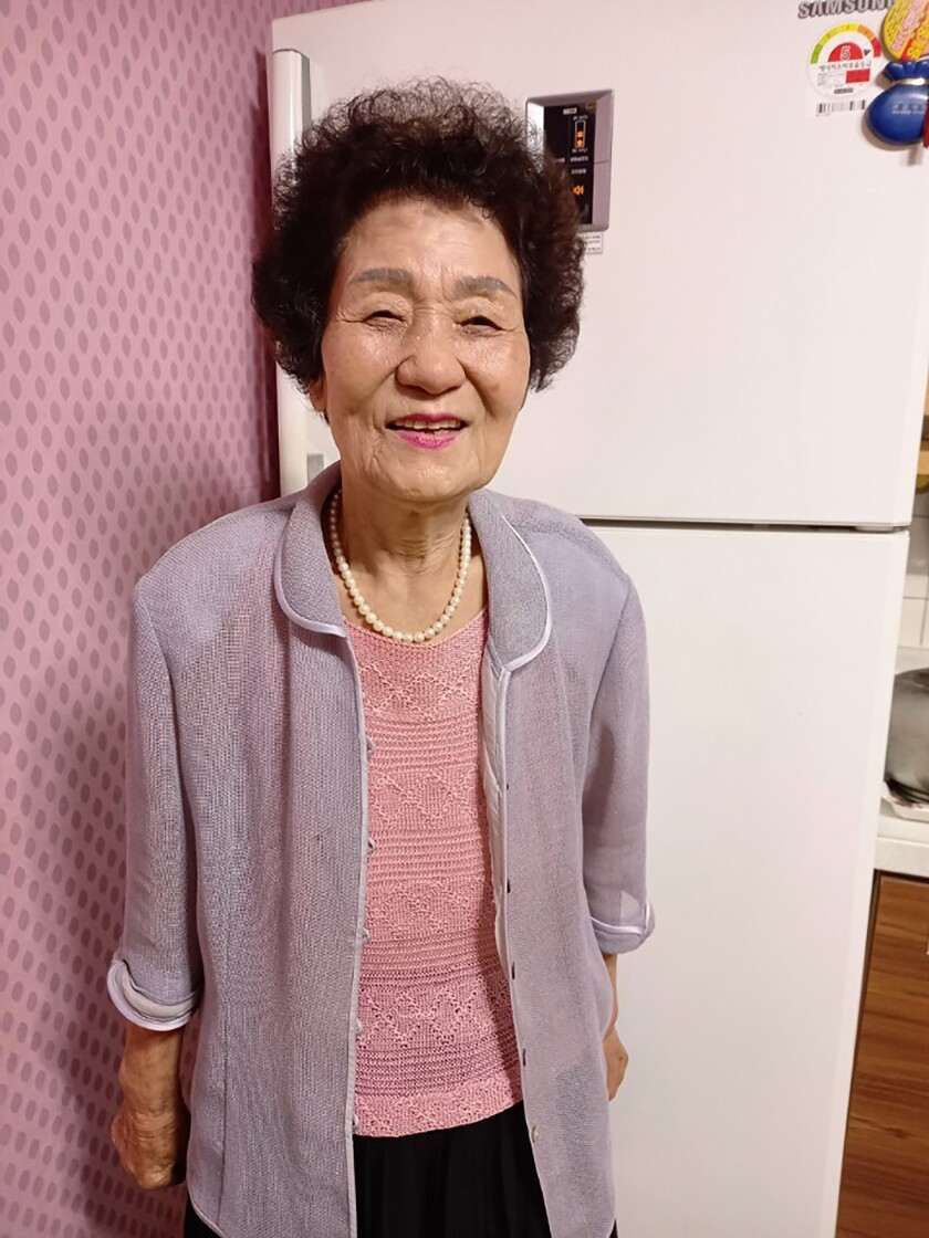 In this photo provided by Kang Myoung Suk, Chung Seong-ran, 84, poses for a photo at her home in Uiseong, South Korea, Wednesday, Sept. 16, 2020. The coronavirus forced Chung to do something new to celebrate South Korea's Thanksgiving holiday instead of being visited by her daughter. With a welfare worker's help, Chung sent a video greeting to her daughter for the first time in her life. (Courtesy of Kang Myoung Suk via AP)