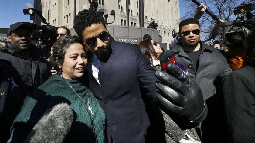 Actor Jussie Smollett takes a selfie with a fan while leaving Cook County Court after his charges we