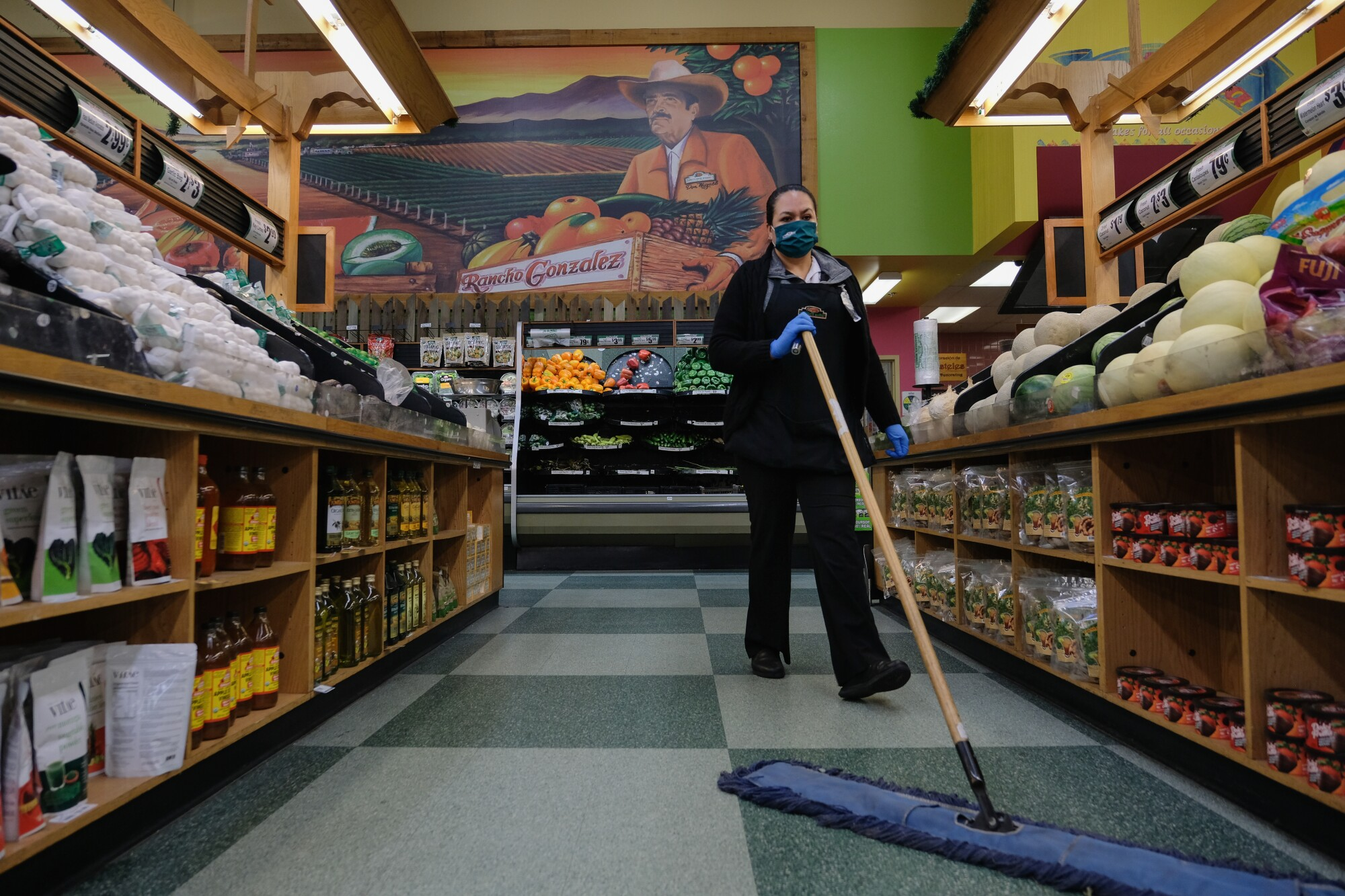 Maria Penuelas sweeps during her morning routine at Northgate Market.