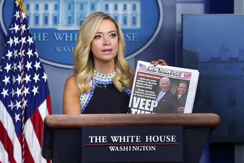 Kayleigh McEnany holds up a tabloid at a press conference