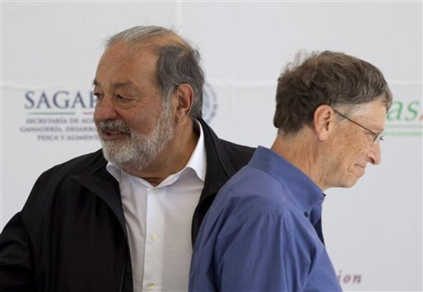 Microsoft Chairman Bill Gates, right, and Mexican telecommunications tycoon Carlos Slim attend the inauguration of a new research center at the International Center for Improvement of Corn and Wheat in Texcoco, Mexico, Wednesday, Feb. 13, 2013. (AP Photo/Eduardo Verdugo)