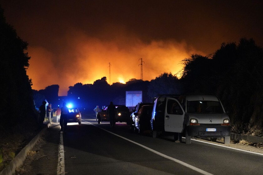 Cars are parked by the road as fires have been raging through the countryside in Cuglieri, near Oristano, Sardinia, Italy, early Sunday, July 25, 2021. Hundreds of people were evacuated from their homes in many small towns in the province of Oristano, Sardinia, after raging fires burst in the areas of Montiferru and Bonarcado. (Alessandro Tocco/LaPresse via AP)