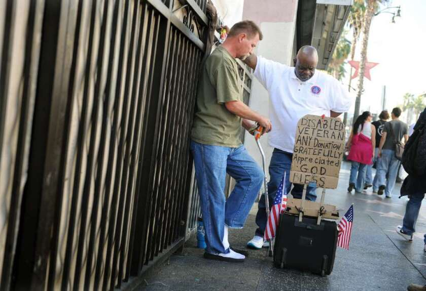 A charity worker speaks with a Vietnam veteran on Sunset Boulevard. An estimated 6,300 veterans who live in Los Angeles County are homeless.