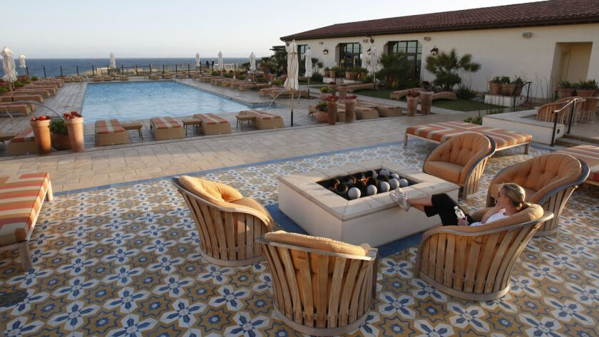 A woman relaxes by the fire pit at the Terranea Spa, at Terranea resort in Rancho Palos Verdes. Union workers collected enough signatures for a ballot measure to require the resort and the nearby Trump National Golf Club to provide panic buttons for workers.