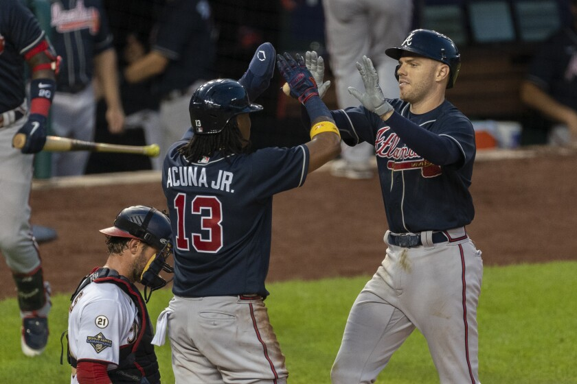 Atlanta Braves' Freddie Freeman, right, is congratulated at home plate by teammate Ronald Acuna Jr. (13) next to Washington Nationals catcher Yan Gomes, left, after hitting a two-run home run during the fourth inning of a baseball game in Washington, Thursday, Sept. 10, 2020. (AP Photo/Manuel Balce Ceneta)