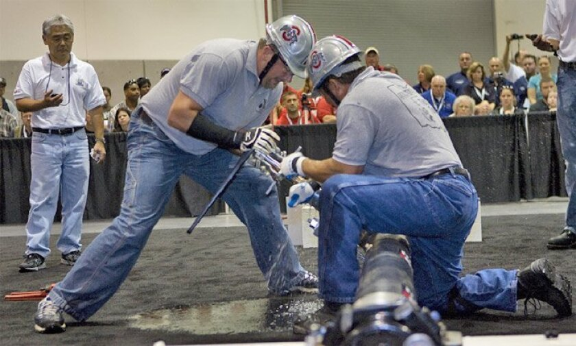 At a water-industry convention yesterday in San Diego, Patrick Crumley (left) and Bruce Farley from Columbus, Ohio, took part in a competition to tap a water main.
