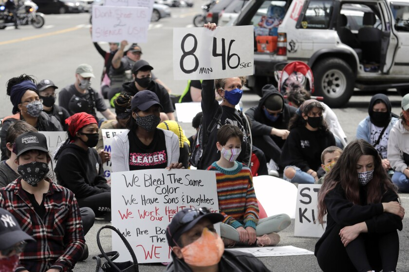"A protester holds a sign that reads ""8:46"" in Tacoma, Wash., during a protest after the death of George Floyd."