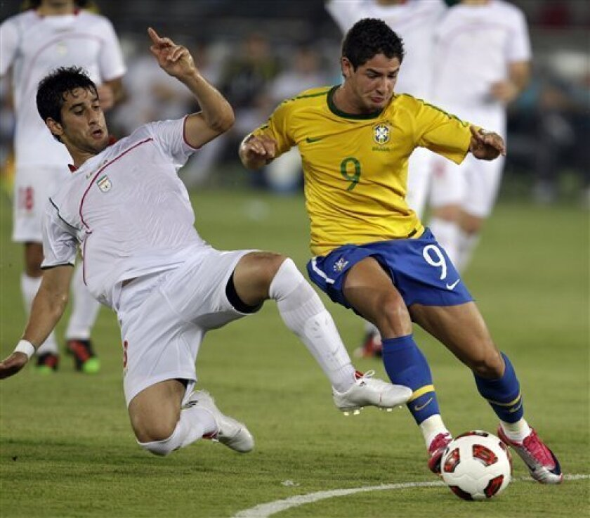 Brazil's Alexandre Pato, right, fights for the ball with Iran's Ehsan Haji Safi during a friendly match in Abu Dhabi, United Arab Emirates, Thursday Oct. 7, 2010. (AP Photo/Kamran Jebreili)