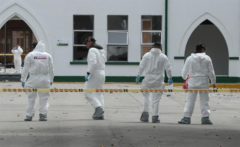 Peritos forenses inspeccionan el lugar donde un carro bomba causó una explosión este jueves en la Escuela General Santander de la Policía en Bogotá (Colombia). EFE