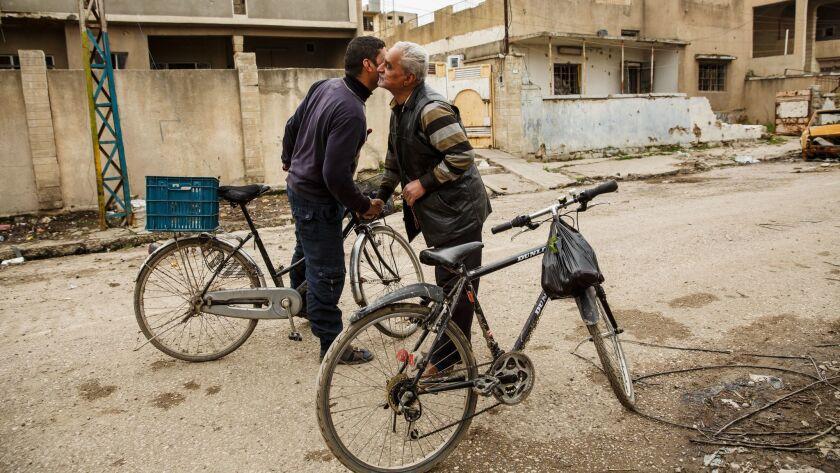 MOSUL, NINEVEH PROVINCE -- SUNDAY, MARCH 19, 2017: Mohammed Kamal Mahmoud greets a friend as he bike