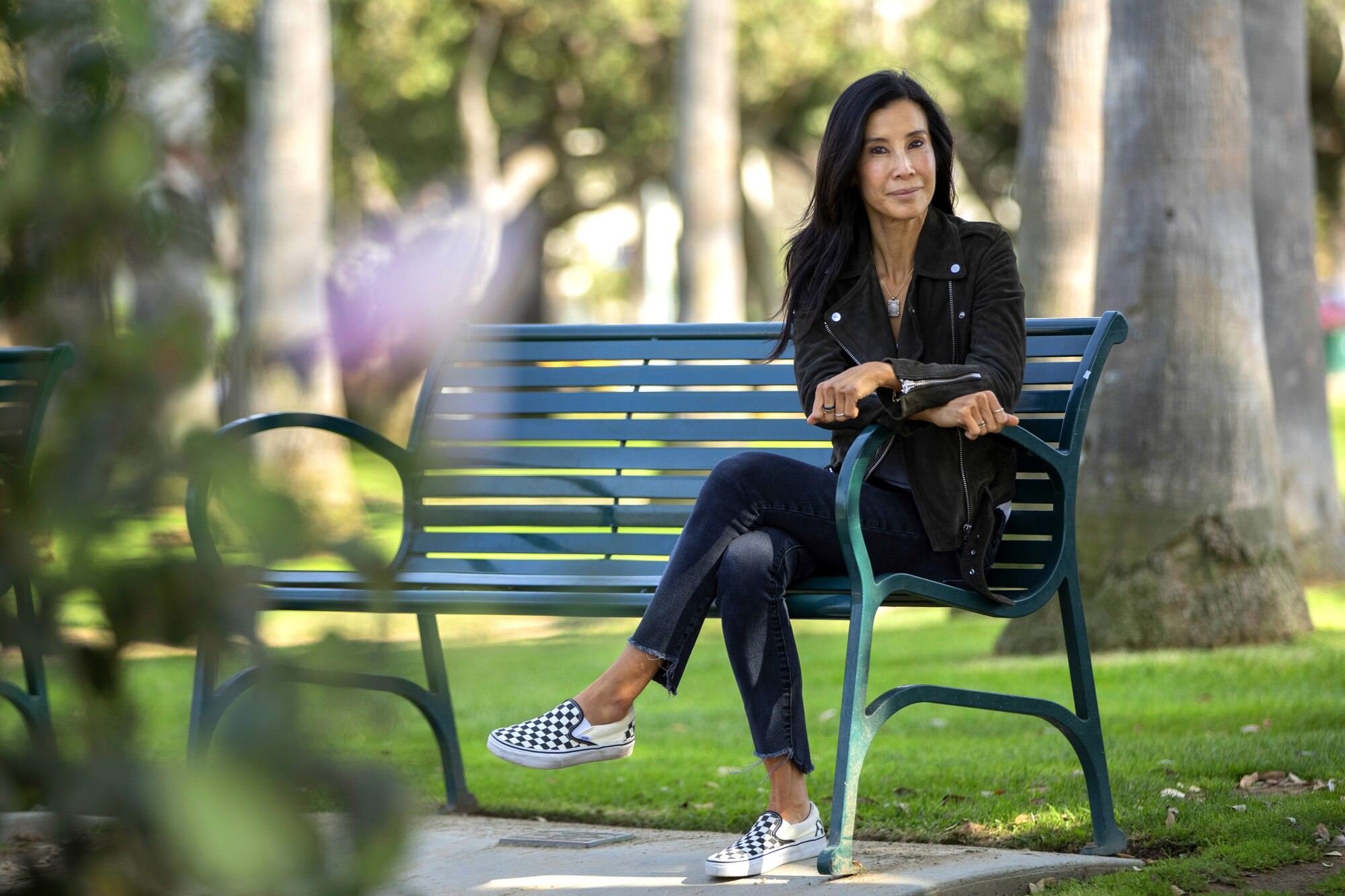 Journalist Lisa Ling sits on a bench in a park.