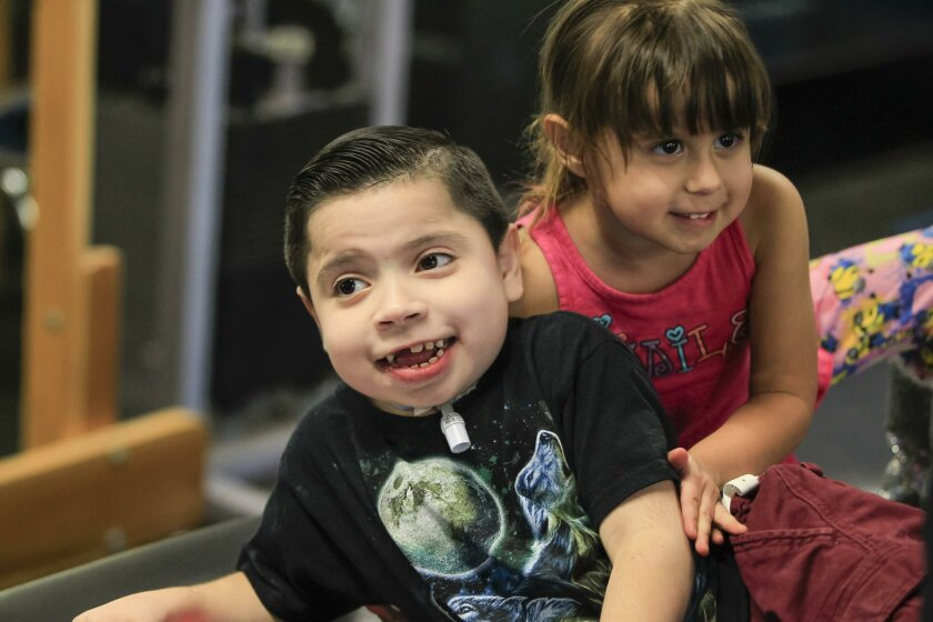 Izaiah Wallis laughs with his sister Caliah, 3, during a therapy visit on Friday at Project Walk in Carlsbad, California. Izaiah was left severely disabled by a drunk driver when he was a baby.