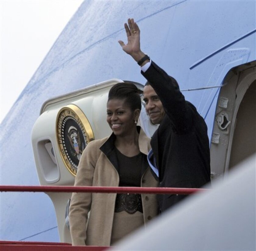 President Barack Obama and first lady Michelle Obama wave as they board Air Force One at Gardermoen Airport in Oslo, Norway, Friday, Dec. 11, 2009. (AP Photo/Susan Walsh)