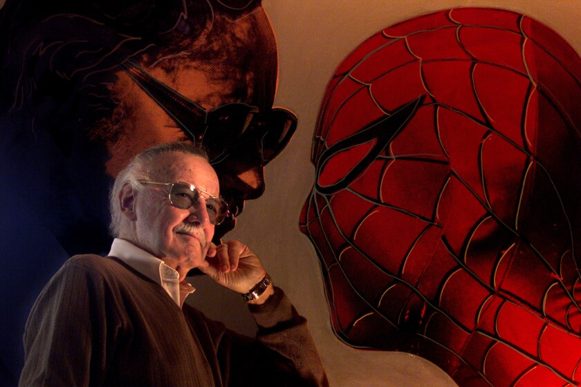 Comic book legend Stan Lee poses with a painting of himself and Spider-Man at his home in Los Angeles in 2002.