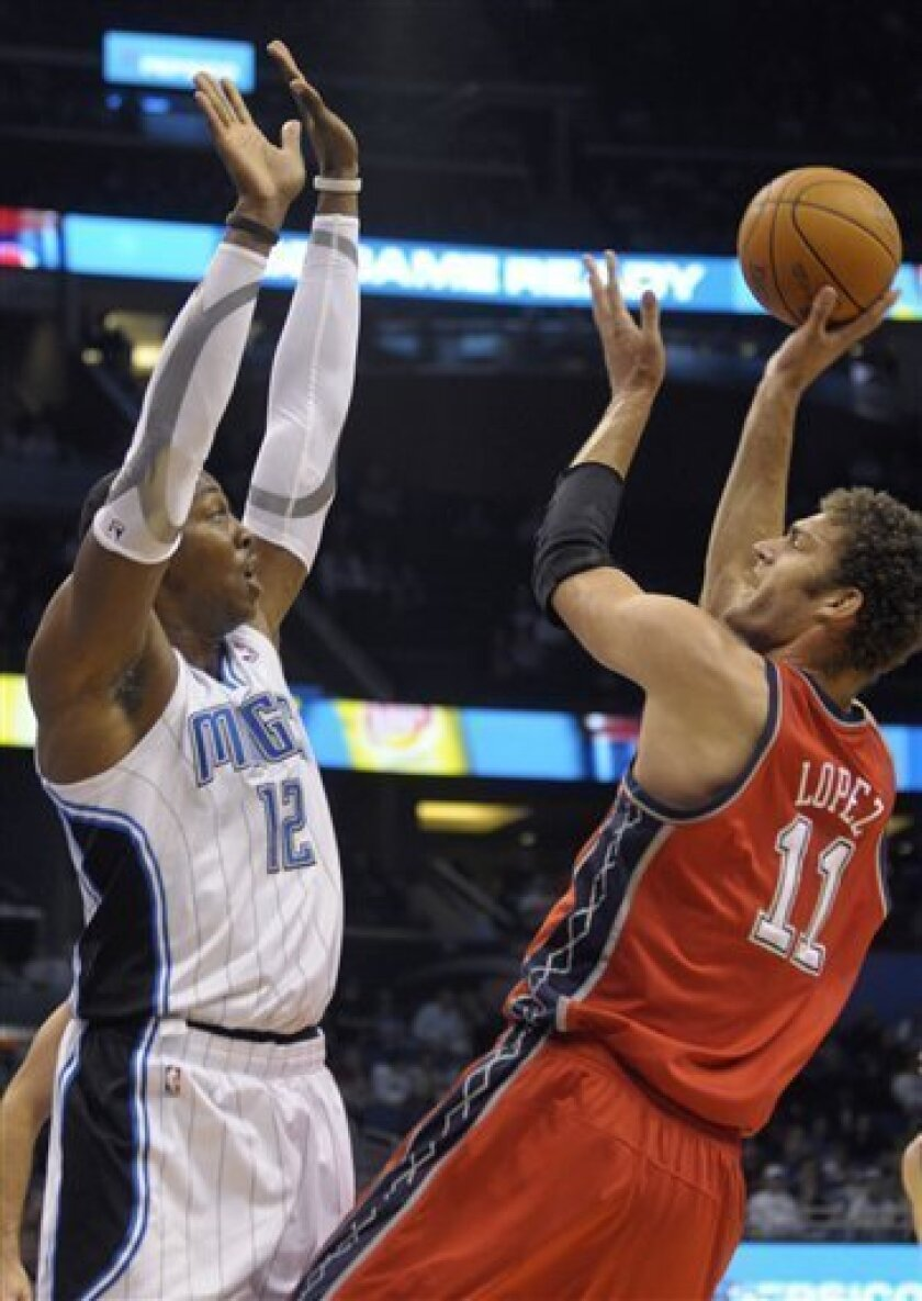 New Jersey Nets center Brook Lopez, right, puts up a shot in front of Orlando Magic center Dwight Howard during the first half of an NBA basketball game in Orlando, Fla., Friday, Nov. 5, 2010. (AP Photo/Phelan M. Ebenhack)
