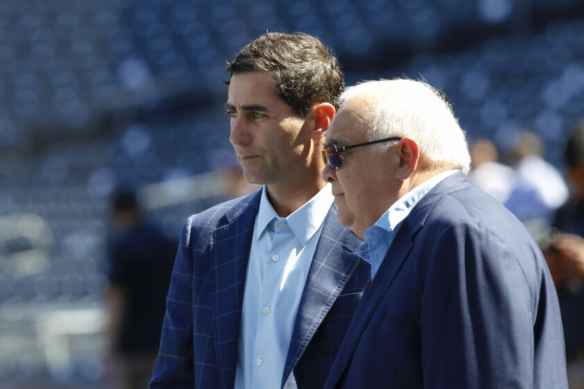 Padres GM A.J. Preller and Ron Fowler, Executive Chairman, watch players during batting practice.