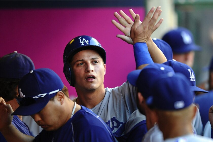 Corey Seager is congratulated by his Dodger teammates after scoring a run against the Angels at Angel Stadium on Sept. 7