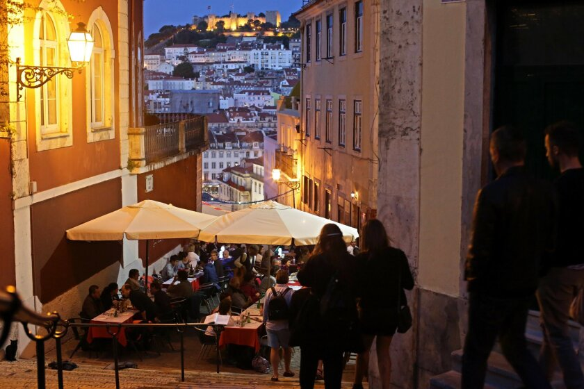 In this May 25, 2016 photo, tourists have dinner at restaurant tables set outside on public stairs with a view of Lisbon's Saint George castle, in the background. With sunny days getting longer and lazier, sparkling beaches warming up and terrorism fears driving customers away from other Mediterran