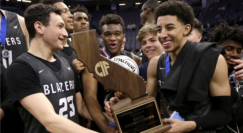 Sierra Canyon's Jacob Miller, left, and Scotty Pippen Jr. right, hold the championship trophy as the Trailblazers celebrate their Open Division state title on March 9.