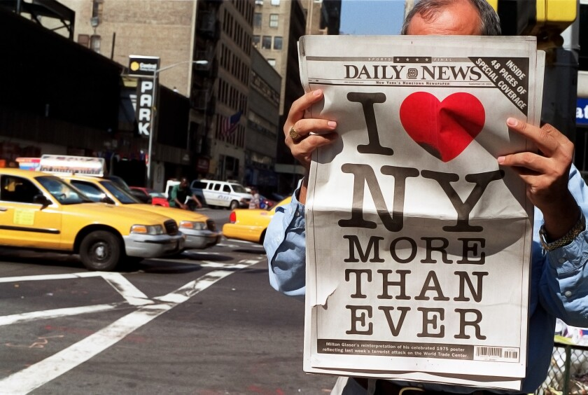 "A man holds up a copy of the New York Daily News with a logo reading ""I Heart New York"""