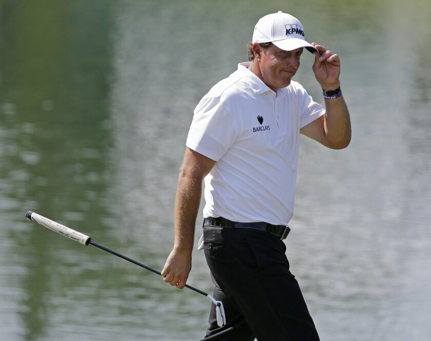 FILE - In this May 12, 2016, file photo, Phil Mickelson tips his hat after making par on the 18th hole during the first round of The Players Championship golf tournament in Ponte Vedra Beach, Fla. In his first public appearance since he was linked to insider trading allegations, Mickelson said Wedn