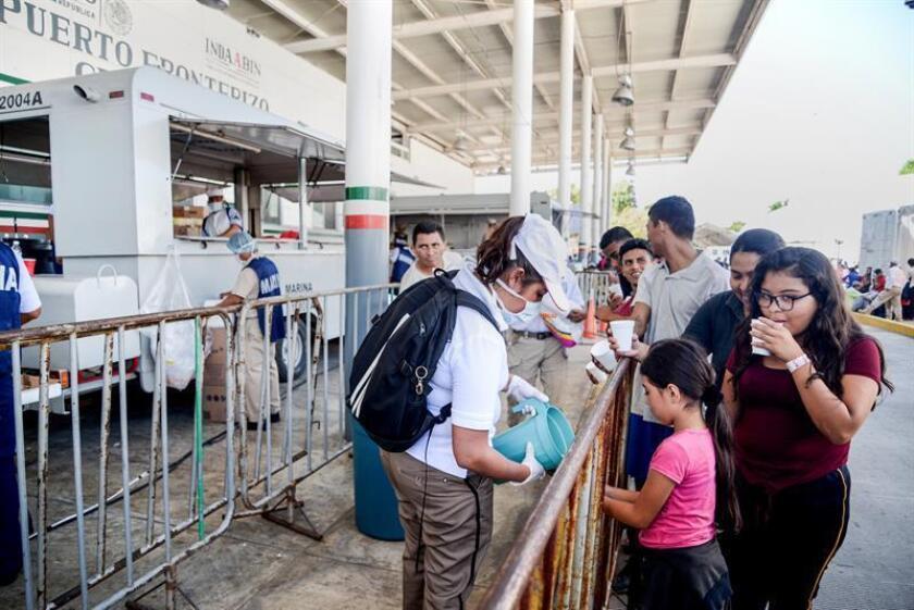 Migrantes hondureños que decidieron acogerse a la tarjeta humanitaria para establecerse de manera legal en territorio mexicano, esperan este martes su documento final, que les permitirá buscar trabajo o ir a la frontera con Estados Unidos en busca de su ingreso a territorio norteamericano, en Ciudad Hidalgo (México). EFE