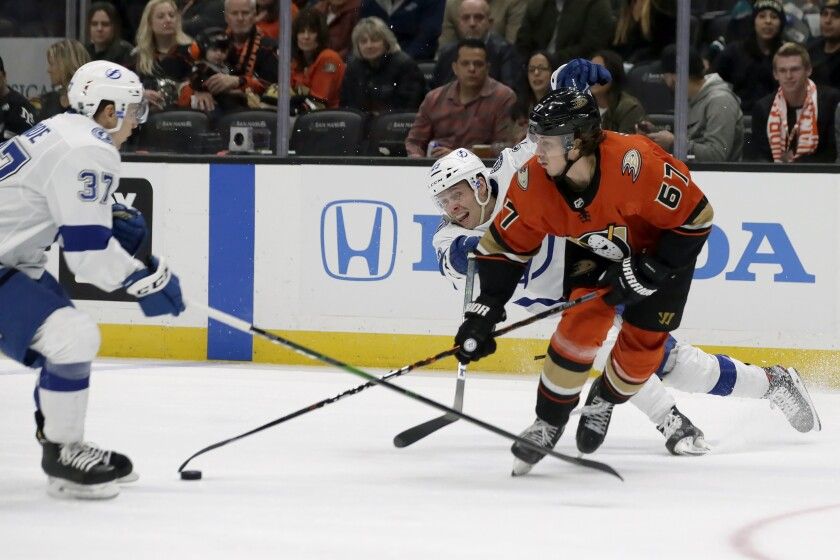 The Ducks' Rickard Rakell (67) vies for the puck against the Lightning's Yanni Gourde, left, and Carter Verhaeghe on Jan. 31, 2020.