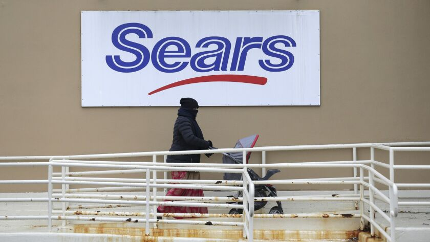 A person walks near a sign for a Sears store in Hackensack, N.J., Tuesday, Jan. 8, 2019. The iconic
