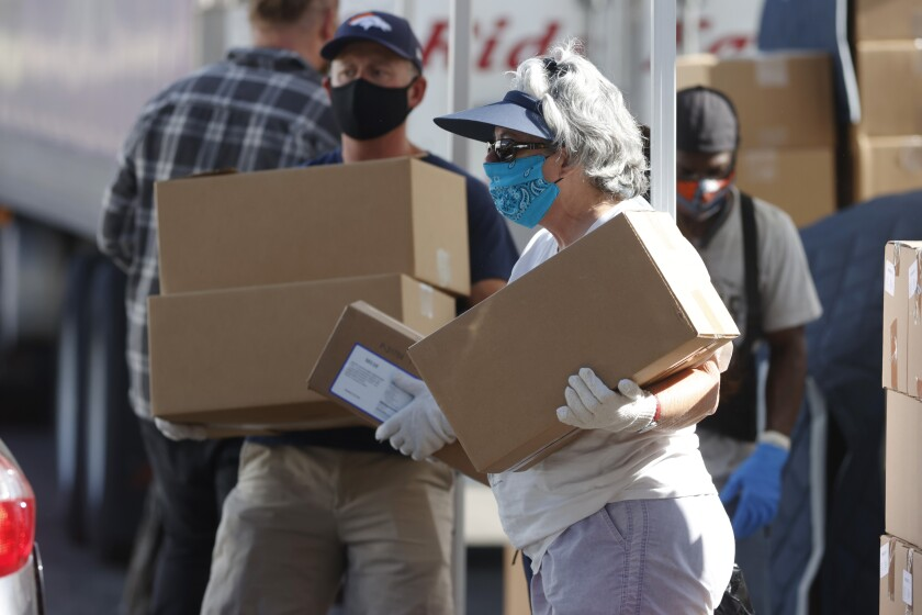 Volunteers carry boxes of food at a large mobile pantry set up by the Food Bank of the Rockies in Denver.