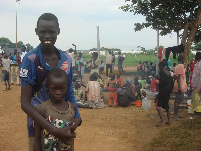 In this photo provided by UNMISS , children pose for a photograph, in Juba, South Sudan at the UN compound in the Tomping area, Tuesday, July 12, 2016. An uneasy calm settled over South Sudan's capital on Tuesday after the country's leader and his top rival both demanded a cease-fire. Renewed fight