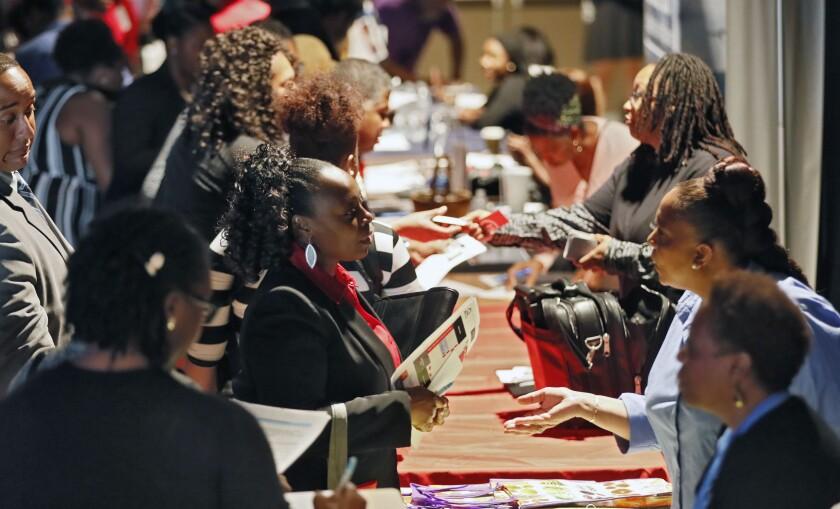 Company representatives talk with potential applicants at a job and resource fair in Atlanta.