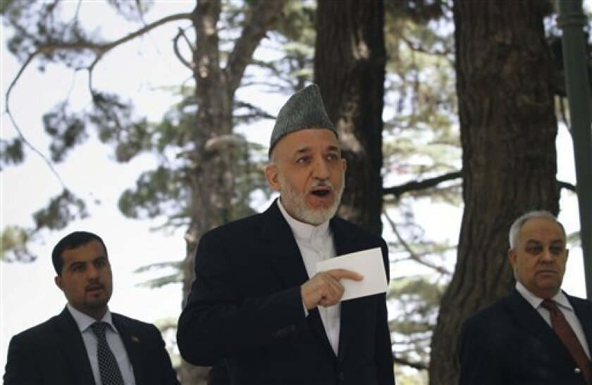 Afghan President Hamid Karzai speaks with a media member after a press conference at the presidential palace in Kabul, Afghanistan on Tuesday, May 31, 2011. Angered by civilian casualties, Karzai said Tuesday he will no longer allow NATO airstrikes on houses, issuing his strongest statement yet against strikes that the military alliance says are key to its war on Taliban insurgents. (AP Photo/Musadeq Sadeq)