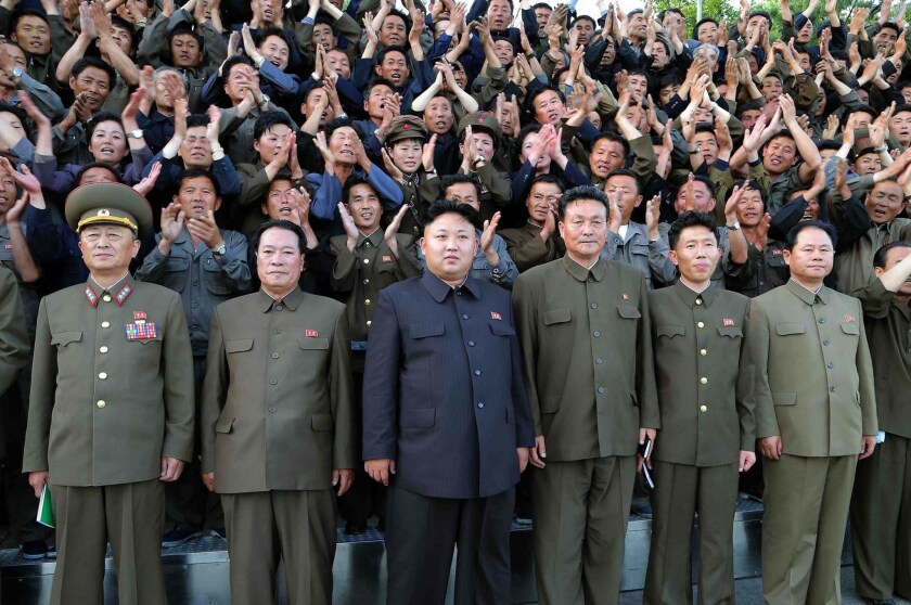 """North Korean leader Kim Jong Un, center, poses at a machine plant. North Korea announced it has sentenced a South Korean Baptist missionary to a life term after convicting him of spying and """"malignantly hurting the dignity"""" of the Kim family."""