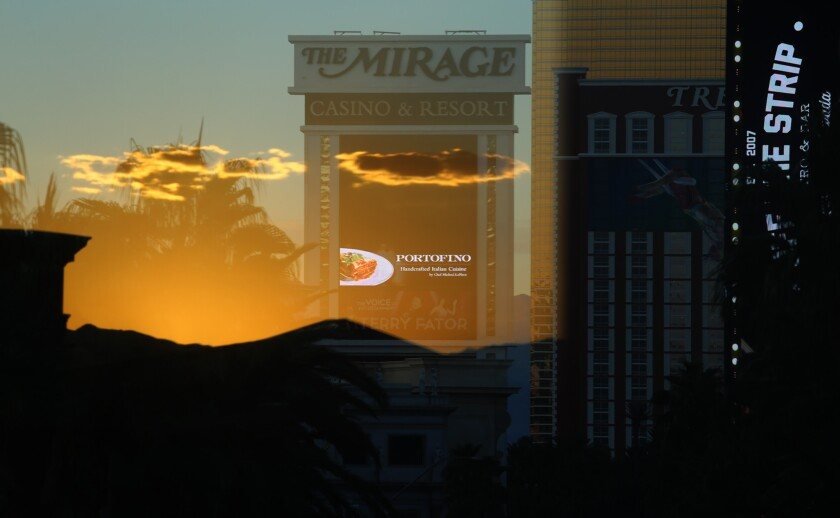 A sunset is reflected against the window of a pedestrian bridge, creating a mirage on the Mirage hotel and casino in Las Vegas. Known for bright lights and gambling tables, Vegas has also served as a literary inspiration.