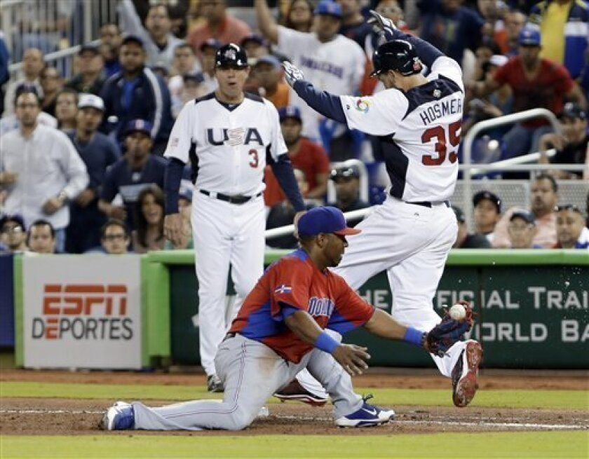 United States' Eric Hosmer (35) is safe at first base as Dominican Republic first baseman Edwin Encarnacion is unable to hold on to the ball during the sixth inning of a second-round game of the World Baseball Classic in Miami, Thursday, March 14, 2013. Jose Reyes was charged with a throwing error. (AP Photo/Wilfredo Lee)