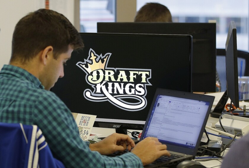 In this file photo, Bear Duker, a marketing manager for strategic partnerships at DraftKings, works at company headquarters in Boston. Daily fantasy sports rivals DraftKings and FanDuel have agreed to merge.